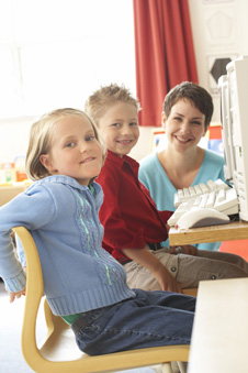 kids and teacher at computer